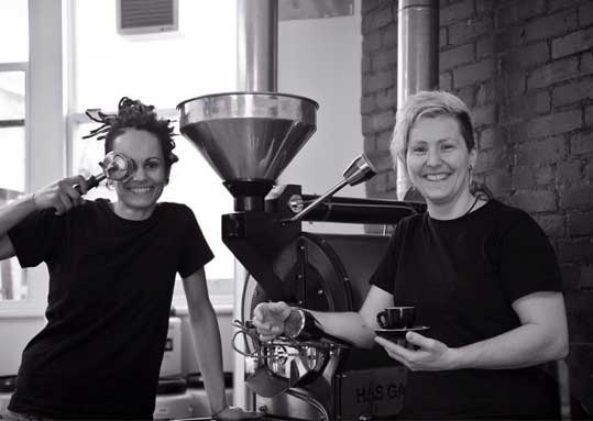 Straight Up Roasters, owners Chicko and Jess are sitting in front of a coffee roaster in Moonah, Hobart, Tasmania. Chicko comically covers her eye with a coffee implement. Jess holds a cup of coffee. They both smile warmly, directly at the camera.