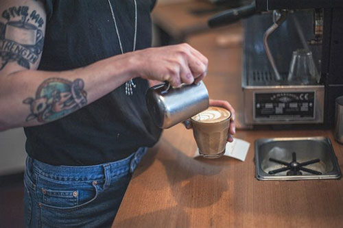 Torso shot of a barista finishing the pour from a stainless steel jug into a perfect latte. The barista is standing behind a large industrial coffee machine at Straight Up Roasters, Moonah, Hobart, Tasmania.